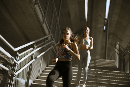 Two young woman workout down stairs in urban environment
