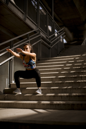 Young fitness woman doing exercises outdoor in urban enviroment