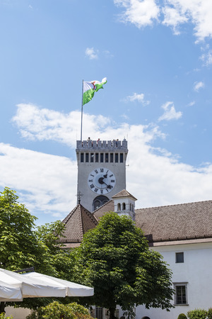 View at clock tower of Ljubljana castle with town flag in Slovenia 에디토리얼