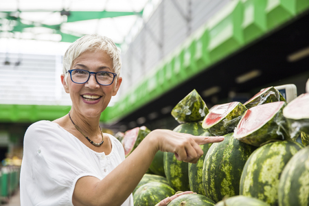 Portrait of senior woman buying watermelon on market Stock fotó