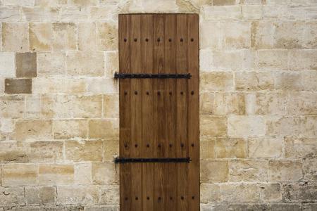 Puerta de madera antigua en el antiguo muro de piedra Foto de archivo