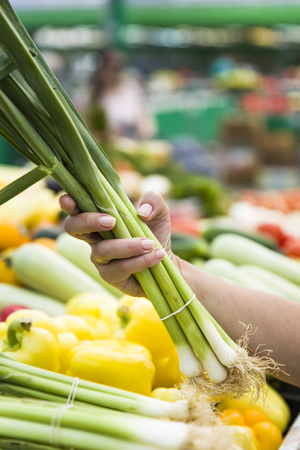 Woman buying fresh bunches of spring onions on stall at the market