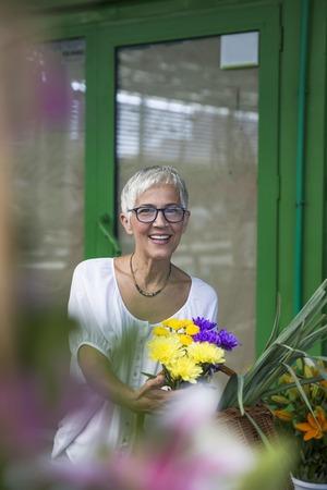 Charrming senior woman buying  flowers on local market