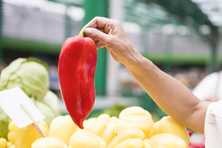 Red pepper in hand on market