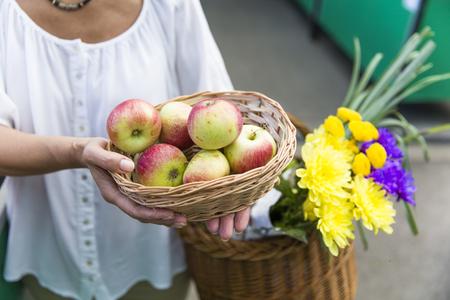 Senior woman with fresh organic apples on market