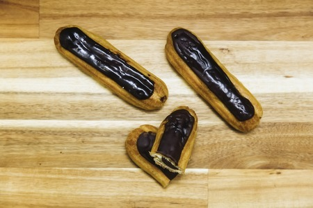 Eclair crispy creamy cake with dark chocolate on wooden background
