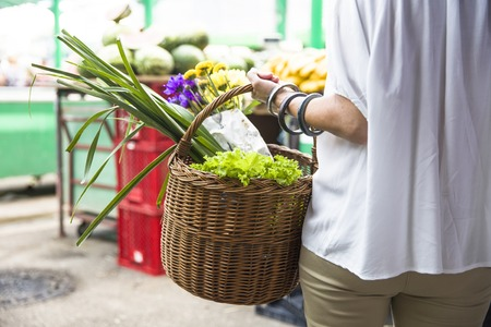 Senior woman holds basket with flowers and vegetables walks at market Stockfoto