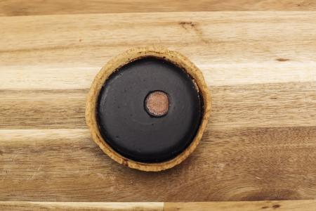 Sweet fresh dark chocolate tart on the wooden table Standard-Bild