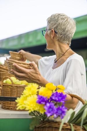 Charming senior woman buying fresh flowers on market