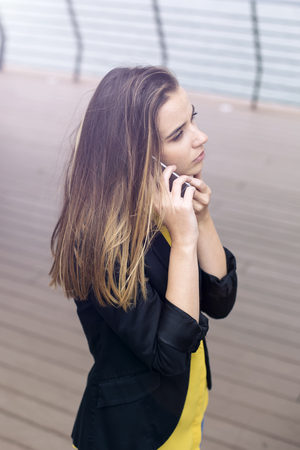Young cheerful business woman uses cellphone at the street