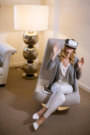 Cheerful young woman playing video games with virtual reality googles at home