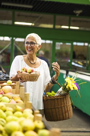 Senior woman with fresh organic apples on market Reklamní fotografie