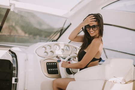Young attractive woman drives a  yacht at sea at sunny day Stock Photo