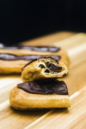 Eclair crispy creamy cake with dark chocolate isolated on wooden background