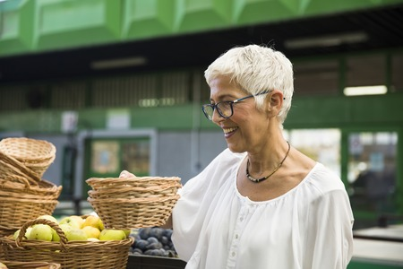 Portrait of senior woman buying fresh organic vegetable on market