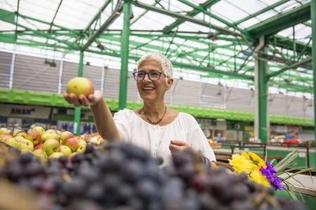 Happy senior woman buying apples on market
