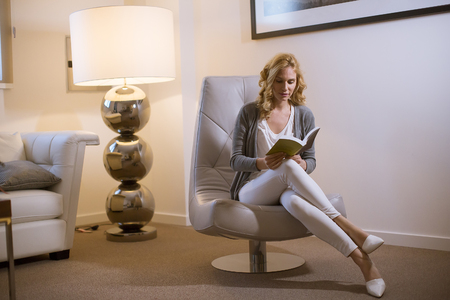 Young woman at home sitting on modern chair in front of modern lamp  and relaxing in her living room reading book