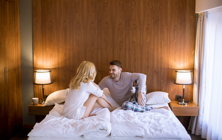 Picture of young loving couple enjoy while sitting in the bed Reklamní fotografie