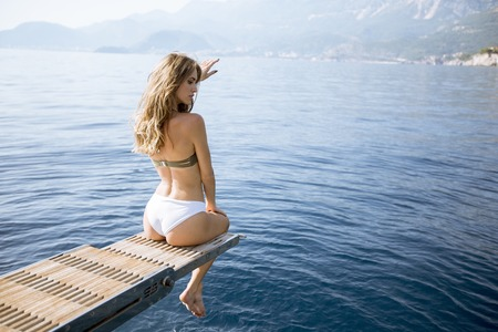 Pretty young woman relaxing on the yacht at sea on a sunny summer day Banco de Imagens - 121419124