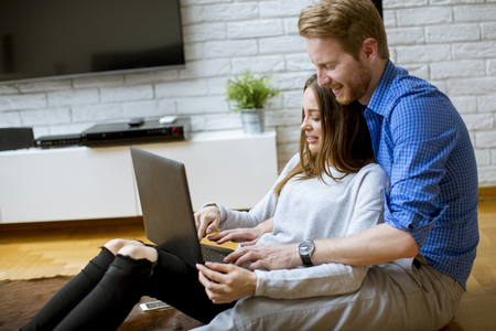 Young couple with a laptop sitting on the floor