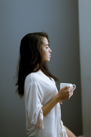 Portrait of attractive young woman with mug by the window in bedroom