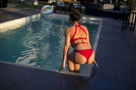 Beautiful young woman in red swimwear relaxing by the  swimming pool
