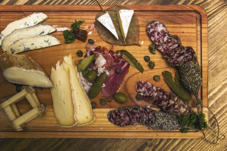 Top view at cheese and sausages as an appetizer served on wooden plate Archivio Fotografico
