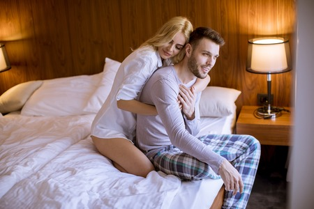Loving and hugged young couple sitting on the bed in the bedroom Stock Photo