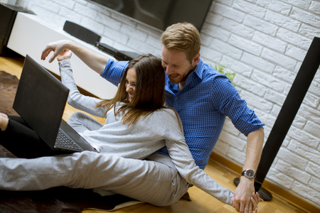 Close up view at young couple using laptop while sitting on the floor in their living room