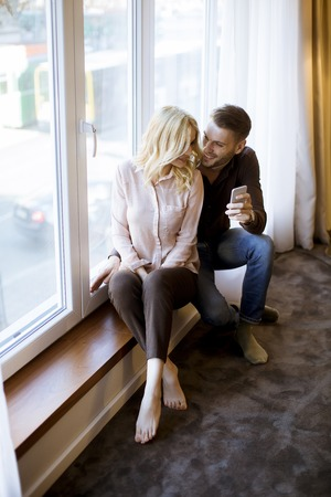 Young loving couple use wireless internet at apartment, sitting near window, enjoy day light and using mobile phone