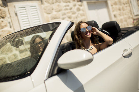 Two happy female friends in white cabriolet car driving everywhere and looking for freedom and fun
