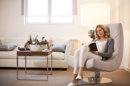 Young woman at home sitting on modern chair  in the room and reading book Фото со стока
