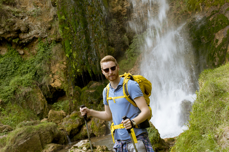 Handsome young hiker stopped beside a mountain waterfall to take a rest