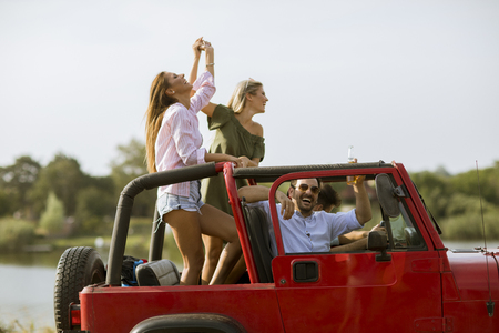 Group of happy young friends having fun in convertible car during summer vacation by river Stockfoto - 120081169