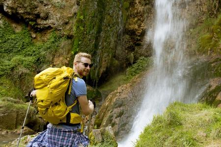 Bel giovane escursionista si fermò accanto a una cascata di montagna per riposarsi