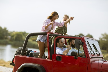 Group of happy young friends having fun in convertible car during summer vacation by river Stockfoto
