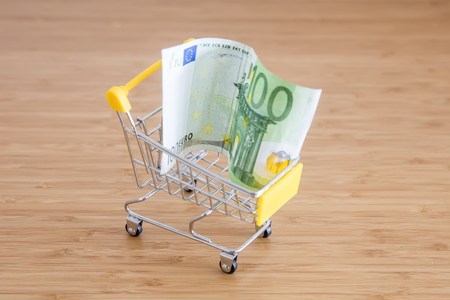 Shopping cart with eur banknote on wooden table