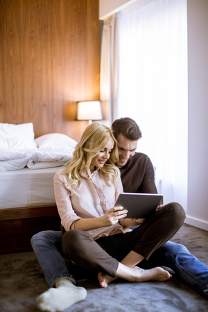 Romantic young happy couple in love sitting on floor resting and  having fun surfing internet