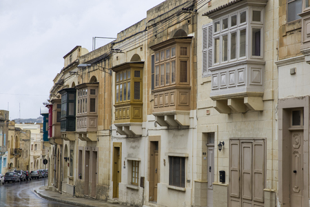 Details of traditional, wooden balcony and stone facade, typical for architecture of Gozo, Malta
