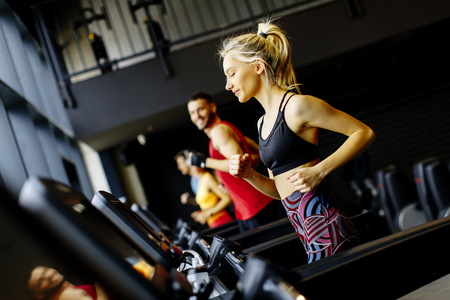 Group of young people running on treadmills in modern gym