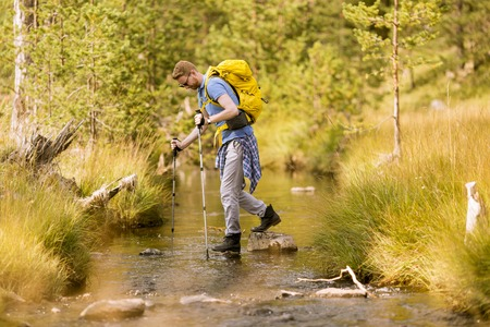 Redhair young man crosses a mountain stream during a hiking on a sunny day