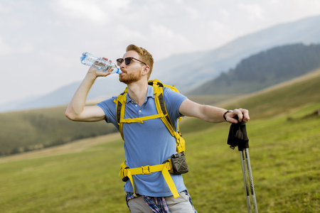 Young handsome hiker stopped and drink water from a bottle