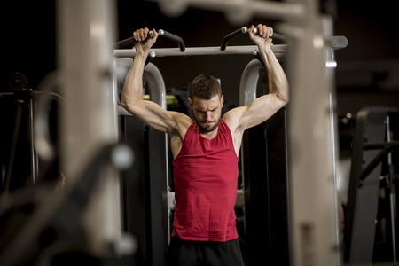 Athletic man doing workouts for a back with power exercise machine in a gym club