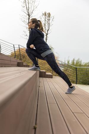 Bella giovane sportiva che fa esercizi di allungamento per le gambe all'aperto