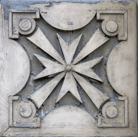 Closeup of the traditional Maltese cross on the facade of old building in Gozo, Malta