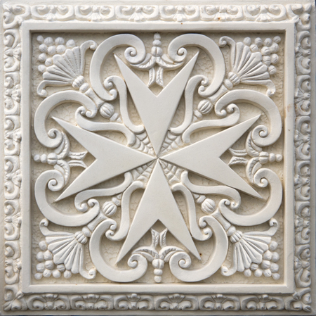 Closeup of the traditional Maltese cross on the facade of old building in Mdina, Malta
