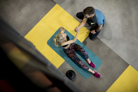 Top view at sporty woman doing exercises with assistance of her personal trainer at gym Standard-Bild