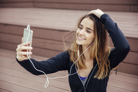 Portrait of young sporty woman taking selfie outdoor