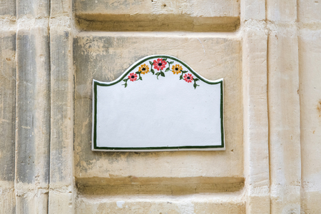 Traditional Maltese home sign board at Gozo, painted on ceramic tile placed on the stone wall without text inside