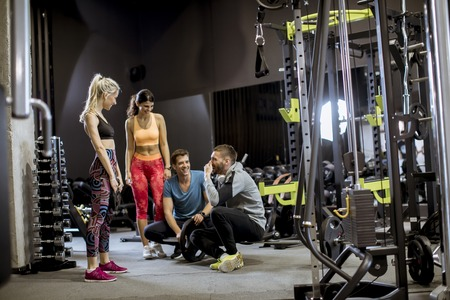 Group of young people in sportswear talking and laughing together while sitting on the floor of a gym after a workout Banco de Imagens